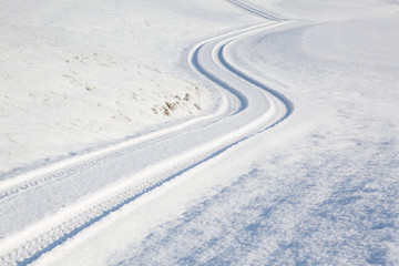 Car tire track on winter road