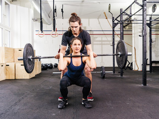 Young woman and trainer doing squats