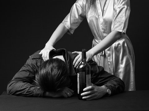 Alcoholism. Drunk man is sleeping on the table with the bottle in the hand, his wife is trying to wake him up. Black and white. Close up