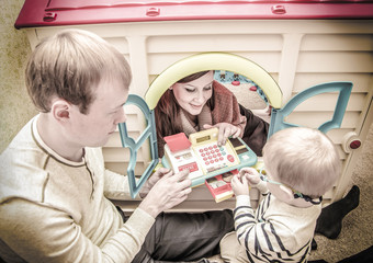 Vintage photo of young family playing with toy cash register in