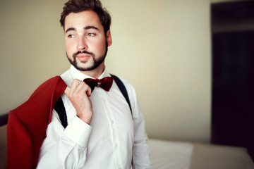 Stylish groom in tuxedo suit marsala red, burgundy bow tie, professional hairstyle, beard, mustache. Wedding preparations, getting ready. Man holding jacket over shoulder. Copy space for text.