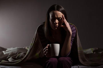Young woman can not sleep. She is sitting on her bed and drinking tea.