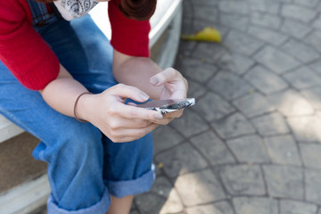 girl wearing jeans looking at the smartphone