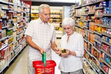 Senior couple holding oil bottle