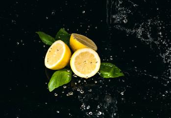 Obraz cytryna polana wodą na czarnym tle - fototapety do salonu