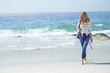 Wall Mural - Beautiful woman walking on beach, barefoot