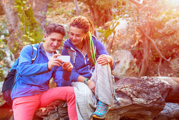 Man and Girl sitting in Forest and looking at Telephone Screen