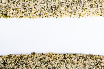 Frame of hulled hemp seeds on white.