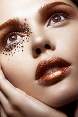 Beautiful girl with a gentle make-up and crystals on the face. Close-up portrait.