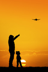 father and son looking the airplane at sunset