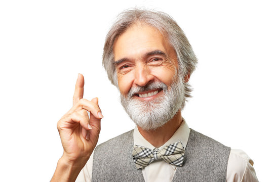 Portrait of handsome senior caucasian man with gray beard and bowtie has an idea pointing finger up isolated on white background