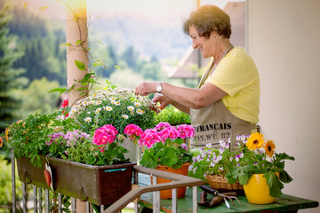 senior woman with flowers on balcony/gardening 08