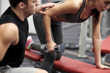close up of couple with dumbbell exercising in gym
