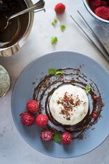 Dessert plating: vanilla panna cotta with chocolate sauce and fresh raspberries