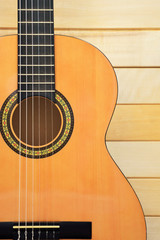 Acoustic guitar closeup front view on wooden background