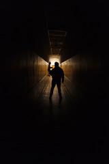 Anti terrorist standing with a gun in the dark corridor