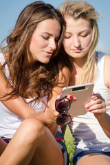 Two happy girlfriends reading interesting post on tablet