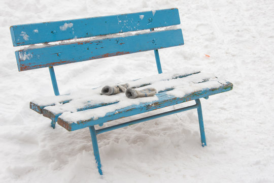 On a snow-covered bench lie forgotten childrens mittens