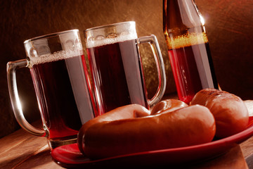 Two mugs filled with beer and hot sausages