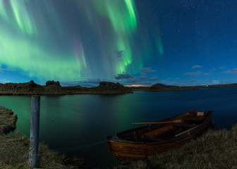 Wall Mural - Aurora borealis in Iceland above a lake with boat