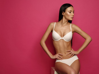 Beautiful young woman with dark straight hair, almond-shaped eyes and bronzed skin is sitting and posing the white basic underwear collection in the studio on the bright pink background