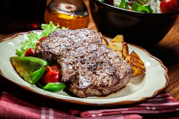 Portions of grilled beef steak with grilled potatoes and paprika