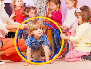 Nice boy play with hoops in kindergarten goup