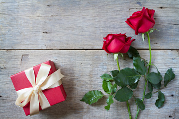 Red roses with red gift box on woonden background. Valentine's D