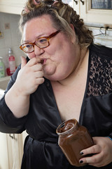 donna obesa sorride mentre si lecca un dito sporco di nutella