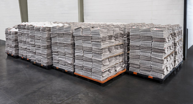 Multiple stacks of newspapers on pallets in warehouse ready to be delivered.