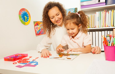 Schoolgirl pieces together a jigsaw puzzle