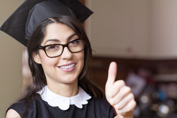 beautiful young woman with dental braces college graduation,thumbs up