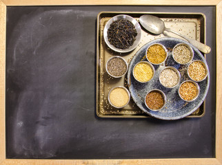 Ancient grain alternatives in silver containers on a chalkboard surface with room for your text.