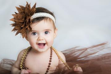 Bebé niña sonriente vestida de bailarina con un tutú marrón y adornos en el pelo