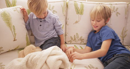 Young blond boy tickling his brother's feet on a sofa