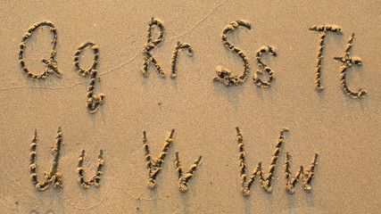 Letters of the alphabet written on sandy beach (from Q to W)