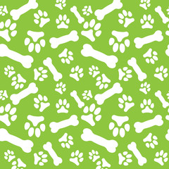 Seamless pattern with white dog paw prints and bones on a green background
