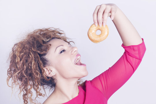 Funny and happy woman eating donut.