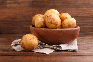 young potatoes in a wooden bowl on a wooden background