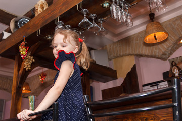 little girl standing on chair in the bar