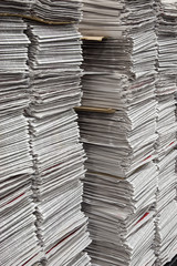Vertical stacks of newspapers in printing warehouse
