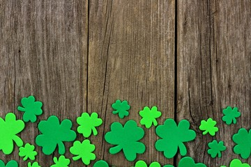 St Patricks Day bottom border of shamrocks over a rustic wooden background