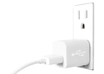 White electrical usb cord and charger plug in wall outlet. High key photo.