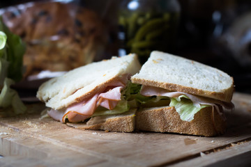 half a ham and cheese sandwich with lettuce on sourdough bread