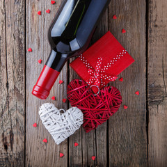Gift , the heart and the bottle of red wine for a romantic holiday Valentine's day on vintage wooden background.selective focus.