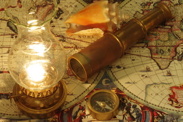 Old telescope, compass, kerosene lamp and seashell lying on an old map of the world.