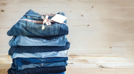 jeans with measure and tag label stacked on a wooden background