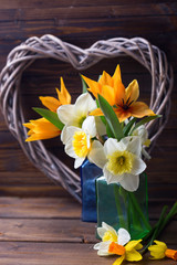 Fresh  spring yellow narcissus and tulips  flowers  in vases and