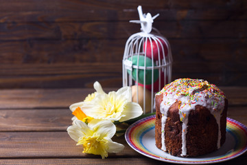 Colorful Easter cake, Easter eggs  and flowers on  dark wooden b