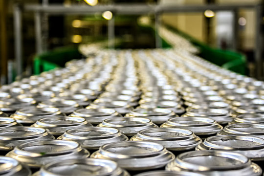 Thousands of shiny aluminum cans on conveyor line